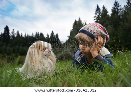 Cute little boy and his dog sitting in the meadow looking at each other. Best friends concept. - stock photo