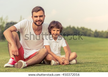 Cute little boy and his handsome young dad are looking at camera and smiling while sitting on the grass in the park - stock photo