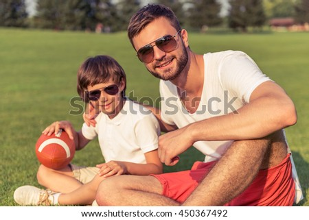 Cute little boy and his handsome young dad in sun glasses are holding a ball, looking at camera and smiling while sitting on the grass in the park - stock photo