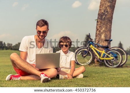 Cute little boy and his handsome young dad in sun glasses are using a laptop and smiling while sitting on the grass in the park. Bicycles in the background - stock photo