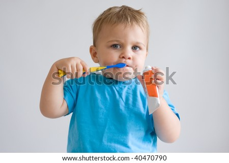 cute, little boy brushing his teeth - stock photo