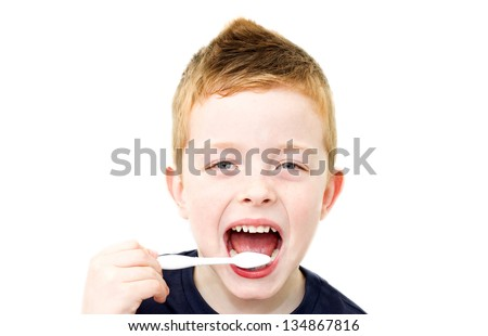 cute little boy brushing his white teeth - stock photo