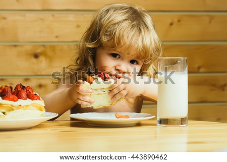 cute little boy child with long blonde hair eating tasty creamy pie or cake with red strawberry fruit and glass of yogurt