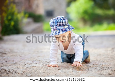 Cute little boy crawling on stone paved sidewalk - stock photo