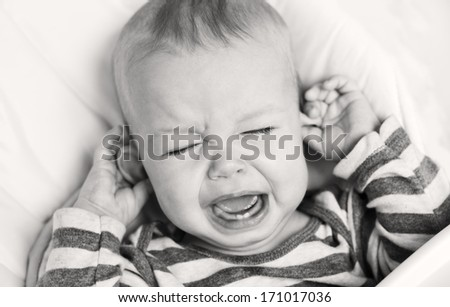 cute little boy crying and holding his ear on a white background ( black and white  ) - stock photo