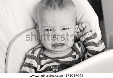 cute little boy crying and holding his ear on a white background ( black and white  )