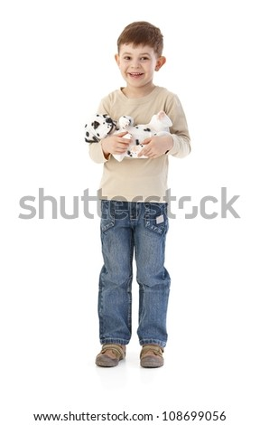 Cute little boy cuddling dog, smiling happily, looking at camera. - stock photo