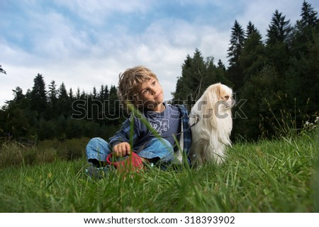 Cute little boy cuddling his dog in nature. - stock photo