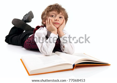 Cute little boy daydreaming while reading book - stock photo