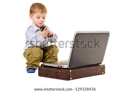 Cute little boy dials on a mobile phone while sitting next to laptop - stock photo