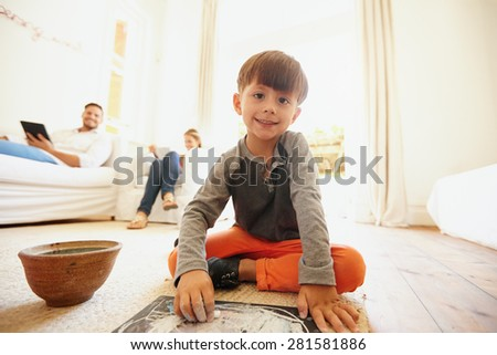 Cute little boy drawing and coloring with his father and mother sitting on sofa using digital tablet. Boy sitting on floor looking at camera while coloring a picture. - stock photo