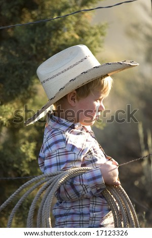 Cute little boy dress in his cowboy gear holding a rope outdoors