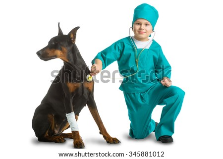 Cute little boy dressed like doctor treated dog or doberman isolated on white background. Veterinary concept - stock photo