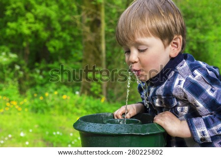 cute little boy drinking from a fountain - stock photo