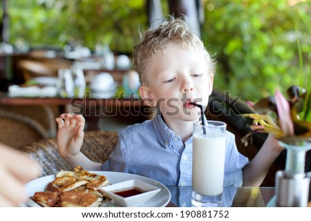 cute little boy drinking his milk at the breakfast, delicious breakfast at the resort - stock photo