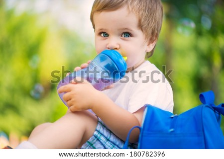 Cute little boy drinking water from bottle - stock photo