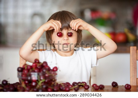 Cute little boy, eating cherries at home in the kitchen, making funny faces and playing with the cherries, having fun - stock photo