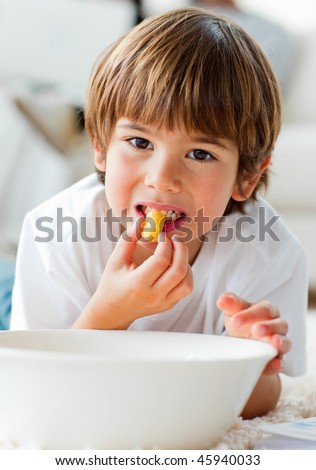 Cute little boy eating chips lying on the floor in the living-room - stock photo