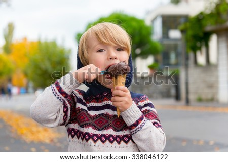 Cute little boy eating chocolate ice cream outdoors - stock photo