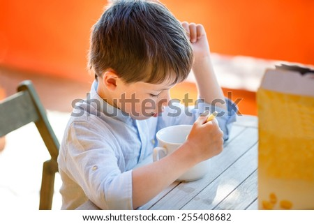 Cute little boy eating dairy breakfast outdoors - stock photo
