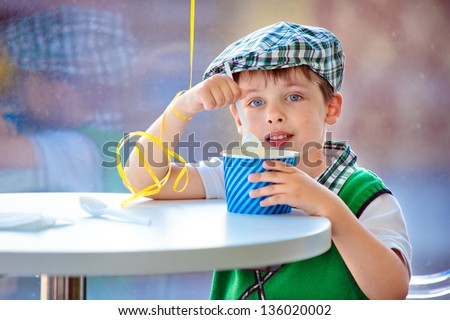 Cute little boy eating ice cream at indoor cafe - stock photo