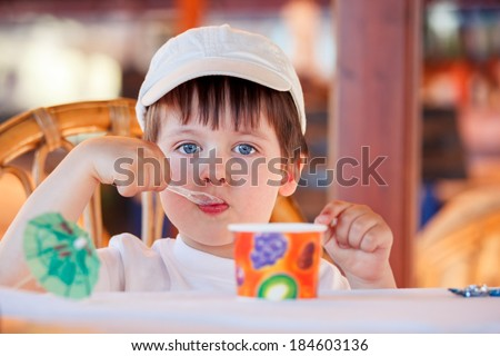 Cute little boy eating ice cream at indoor cafe on beautiful summer day - stock photo