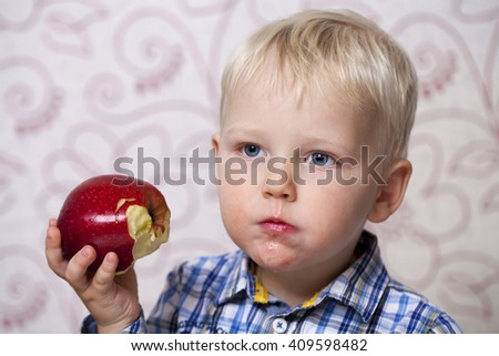 Cute little boy eating red apple at home - stock photo