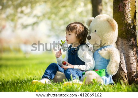 Cute little boy, eating strawberry in the park on a spring sunny afternoon, together with his big teddy bear