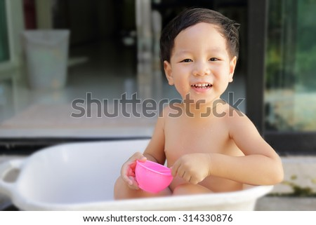 Cute little boy enjoy playing water at home - copy space