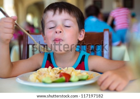 Cute little boy enjoying food - stock photo