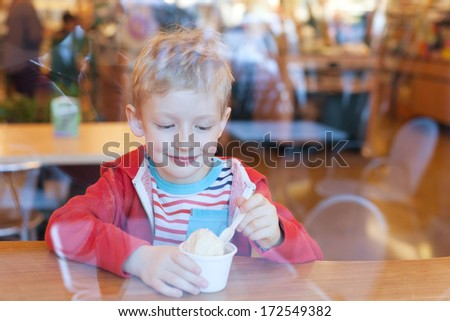 cute little boy enjoying ice cream in cafe, view from outside - stock photo