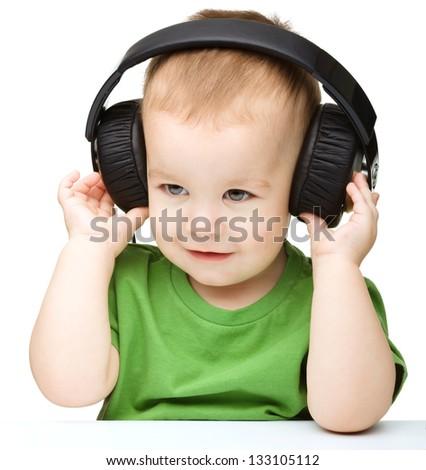 Cute little boy enjoying music using headphones, isolated over white - stock photo