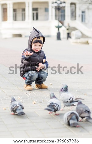 cute little boy feeds the pigeons in the square