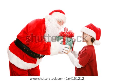 Cute little boy getting a Christmas gift from Santa Claus.  Isolated on white.