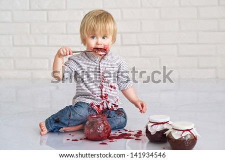 Cute little boy got messy eating strawberry jam from glass jars - stock photo