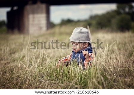 Cute little boy happily sitting in the grass - stock photo