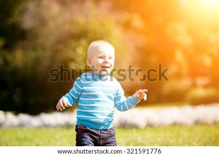 cute little boy having fun in autumn park - stock photo