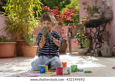 Cute little boy having fun painting and drawing with colorful finger paints outdoors. Children's creativity, developing imagination and artistic sense, do it yourself concept. - stock photo