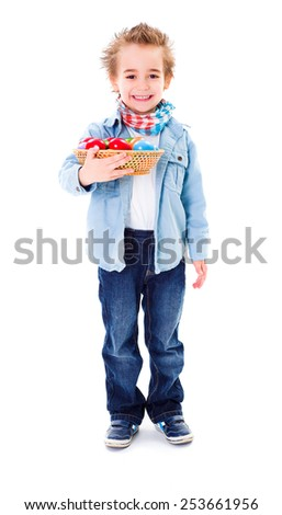 Cute little boy holding a basket with colorful painted Easter eggs - stock photo