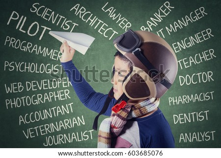 Cute little boy holding a paper plane and wearing helmet with his dreams on the chalkboard in class