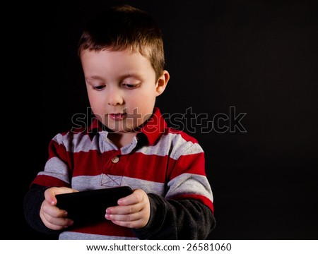 Cute little boy holding a portable video game