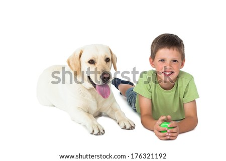 Cute little boy holding ball lying on floor with his labrador on white background