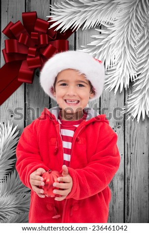 Cute little boy holding bauble against wood with festive bow