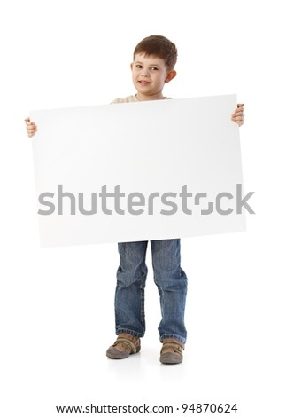 Cute little boy holding big blank sheet, smiling.? - stock photo