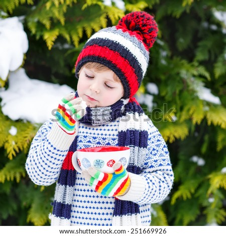 Cute little boy holding big cup with snowflakes and hot cocoa and chocolate drink and marshmallows. Kid boy in winter sweater, hat, long warm scarf and colorfull gloves. On cold snowy winter day. - stock photo