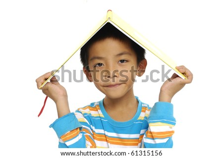 Cute little boy holding book on head - stock photo
