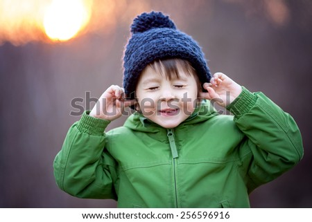 Cute little boy, holding his hands over ears not to hear, making sweet funny face - stock photo
