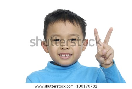 Cute little boy holding up the peace sign, wearing blue t-shirt blue on a white background - stock photo