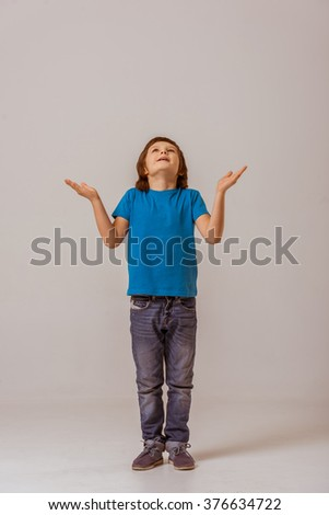 Cute little boy in a blue t-shirt looking up and stretching hands out while standing on a gray background - stock photo