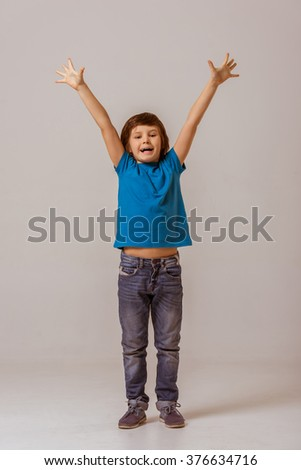 Cute little boy in a blue t-shirt showing happiness with stretched out hands, looking in camera and smiling while standing on a gray background - stock photo
